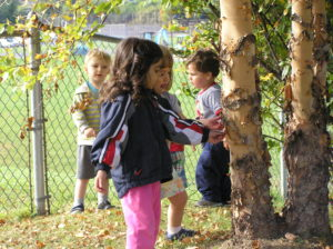 Photo: toddlers exploring the center's enclosed backyard