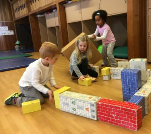 Photo: Preschool children playing on the floor with cardboard blocks