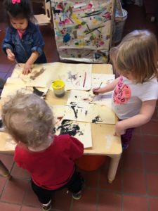 Photo: toddlers standing at a table painting